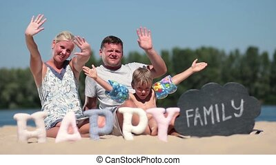 Happy family sitting on the beach and waving hello
