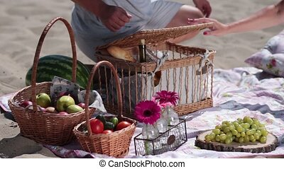 Picnic basket on colorful blanket on the beach and wooden...
