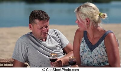 Smiling couple enjoying picnic on the beach