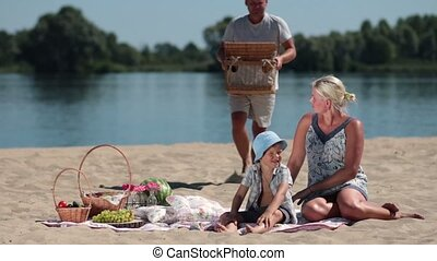 Happy family having picnic on the beach