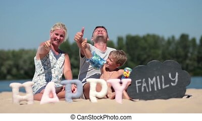 Family sitting on the beach and giving thumbs up