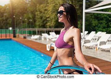 Delighted woman going in the swimming pool - Get energy of...