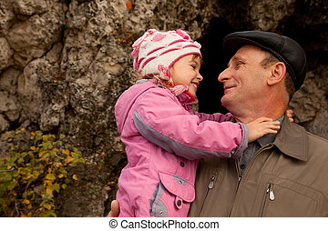Grandfather hold granddaughter in his nahds near the stone wall