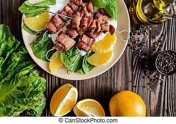 Grilled skewers made with pork and bacon on lettuce with sour cream, sauce and oranges