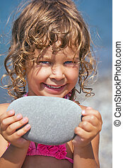 smiling pretty little girl holds in hands pebble on seacoast in afternoon
