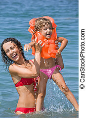 young woman keeps in hands little girl in lifejackets in sea on resort