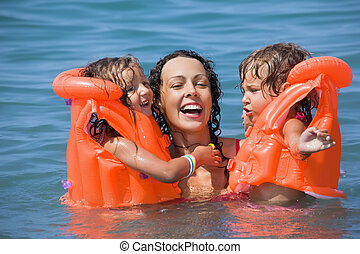 two little girls bathing in lifejackets with young woman in...