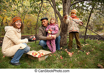 Mother, daughter, son and grandfather in fruit garden
