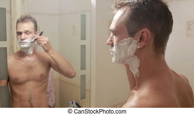man shaves his face. handsome man shaving in the bathroom. -...