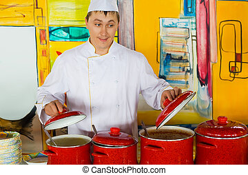 cheerful cook in uniform near red pans in public catering...