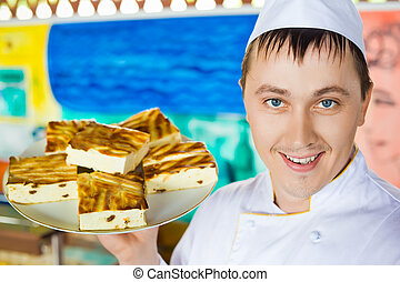 cheerful cook in uniform holding cheese baked pudding on dish