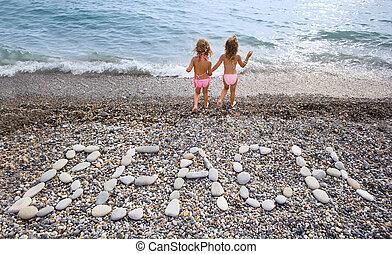 Inscription from stones BEACH at stony coast, two pretty...