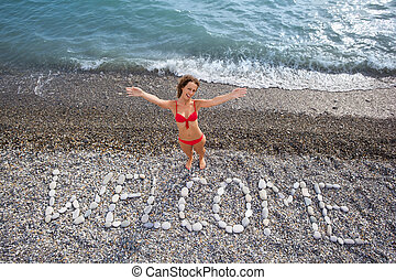 Inscription from stones WELCOME at stony coast, young woman...