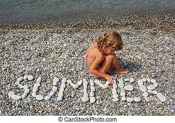 Little girl sits on beach near to water. From stones word is...