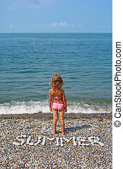 Little girl stands on beach near water From stones word is...