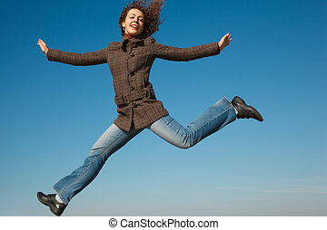 Girl in coat and jeans in jump against blue sky. In bright autumn day.