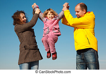 Happy girl shakes on hands at parents against blue sky, in solar autumn day.