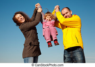 Happy girl shakes on hands at parents against blue sky, in...