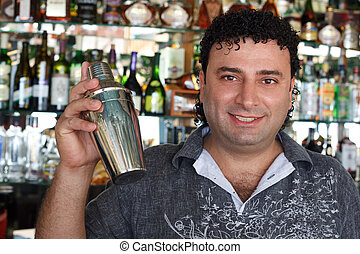 Barman with shaker behind bar rack. Smiling man against...