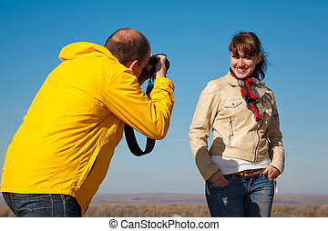 Girl poses for photographer, photosession on nature Hobby...