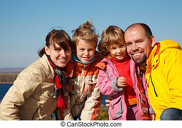 Family of four sunny autumn day Everyone looks into camera