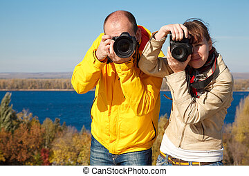 Man and girl photographed in nature. Lenses aimed at viewer.