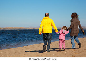 Family of three people walking along beach. View from back.