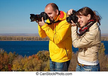 Man and girl photographed outdoors on sunny autumn day.