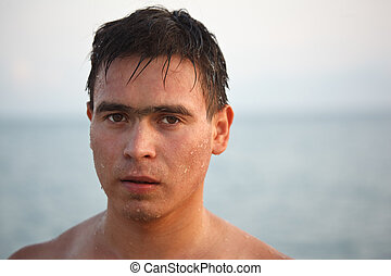 Portrait of man come up from water, on background of the sea...