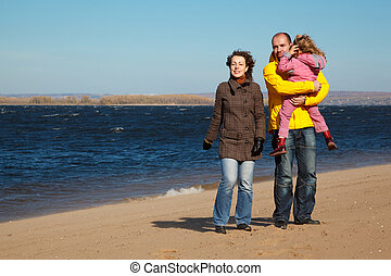 Parents with little girl walk on autumn beach. Productive leisure in open air.