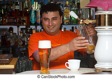 Bartender fills glass of beer. Smiling man against shelves...