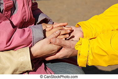 United hands of adults and child as symbol of family unity....