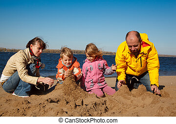 Boy and girl with their parents play in sand on beach, sunny autumn day. Build a castle of sand.