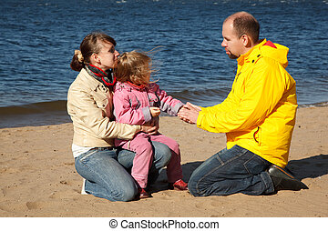 Little girl with her parents at beach, sunny autumn day...