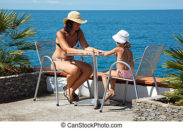 Little girl with her mother in bathing suits sitting at table under open sky beside sea.