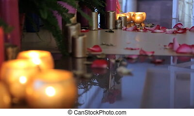Burning candles in glass vase stand on floor. Rose petals...