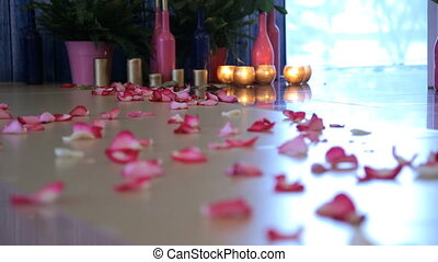 Lots of rose petals are straggled on parquet floor. Flower...