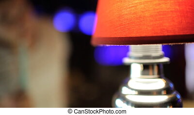 Red coloured lamp shines in dark room during night party. It...