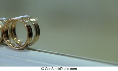 Two bridal golden rings stand on white windowsill. They are...