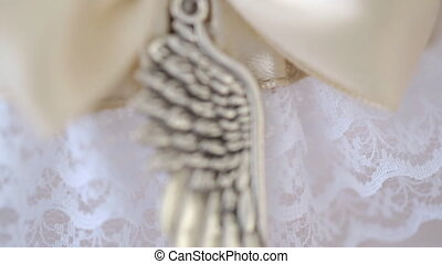 Decorative metal element is sewn to light pink silk ribbon....