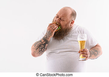 Fat guy biting unhealthy sandwich - Thick bearded man is...