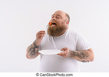 Hungry thick guy eating tiny vegetable - Fat man is enjoying...