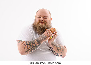 Fat man eating cheeseburger with enjoyment - Greedy male...