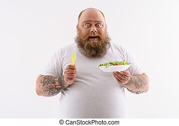 Cheerful thick guy enjoying healthy food - Joyful fat man is...