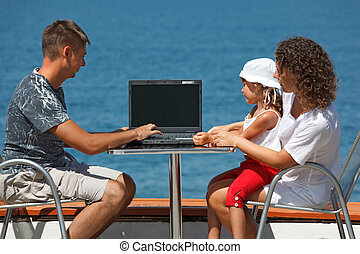 Family of three people sitting at table with laptop on background of sea. Daughter sits on his lap mother.