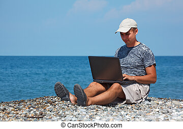 Man in cap sitting on beach with laptop on his knees against...