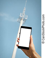 Smartphone in hand. - Smartphone in hand on background tower...