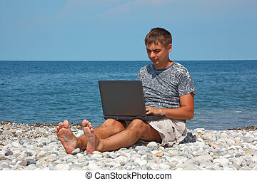 Man sitting on beach with laptop on his knees against...