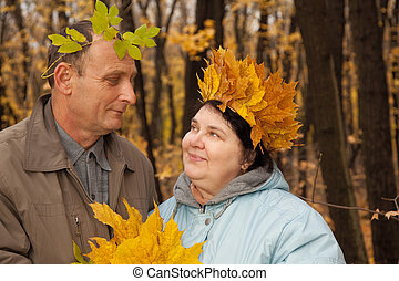 Old man and old woman with wreath of maple leaves look...