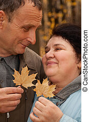 Old man and old woman hold maple leaves and look against...